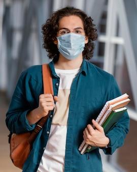 Porträt des jungen männlichen studenten, der eine medizinische maske trägt