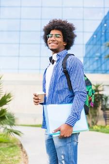 Porträt des jungen männlichen studenten, der in der hand die wegwerfkaffeetasse und bücher stehen gegen campus hält