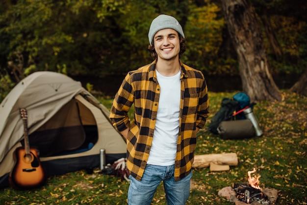 Porträt des jungen männlichen touristen, der im wald mit zelt steht