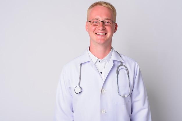 Porträt des jungen mannarztes mit dem blonden haar, das brillen gegen weiße wand trägt