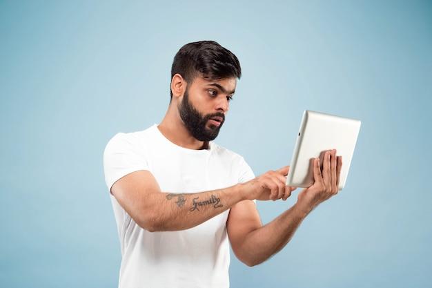 Porträt des jungen mannes auf blauer wand mit tablette