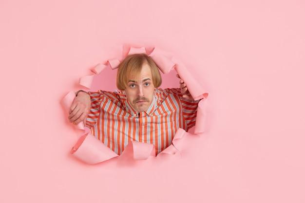 Porträt des jungen mannes auf rosa zerrissenem durchbruchhintergrund
