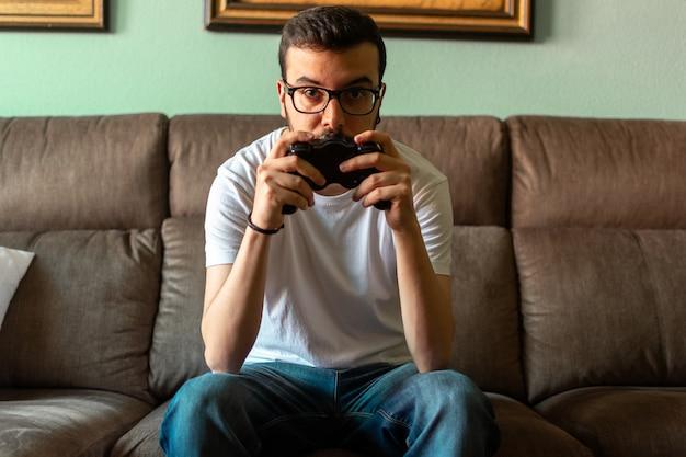 Porträt des jungen mannes das videospiel spielend, das drahtlosen prüfer in seinem haus hält.