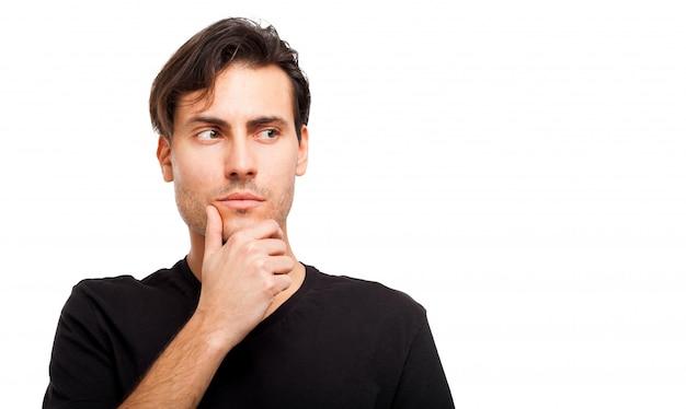 Porträt des jungen mannes denkend gegen ein weiß