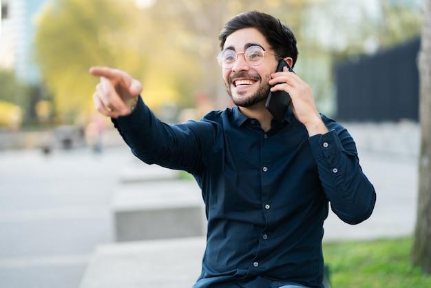 Porträt des jungen mannes, der am telefon spricht und auf etwas zeigt, während er draußen auf der bank sitzt. urbanes konzept.
