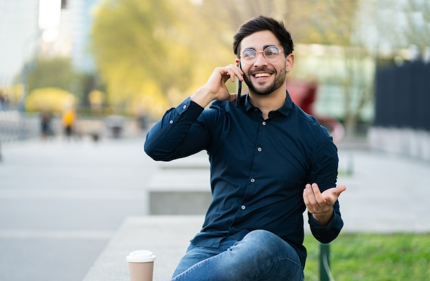 Porträt des jungen mannes, der am telefon spricht, während er draußen auf der bank sitzt. stadtkonzept.