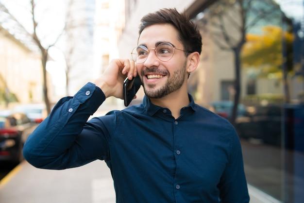 Porträt des jungen mannes, der am telefon spricht, während er draußen auf der straße geht. urbanes konzept.