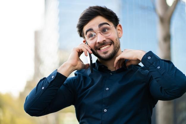 Porträt des jungen mannes, der am telefon spricht, während er draußen auf der straße steht. stadtkonzept.