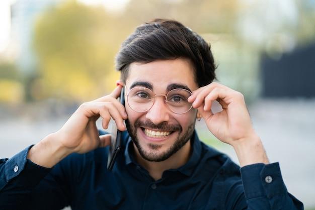Porträt des jungen mannes, der am telefon spricht, während er draußen auf der straße steht. urbanes konzept.