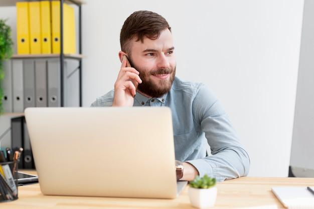 Porträt des jungen mannes, der am telefon spricht