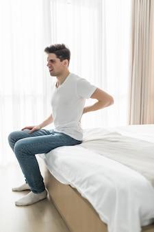 Porträt des jungen mannes, der auf bett sitzt und zu hause unter rückenschmerzen leidet