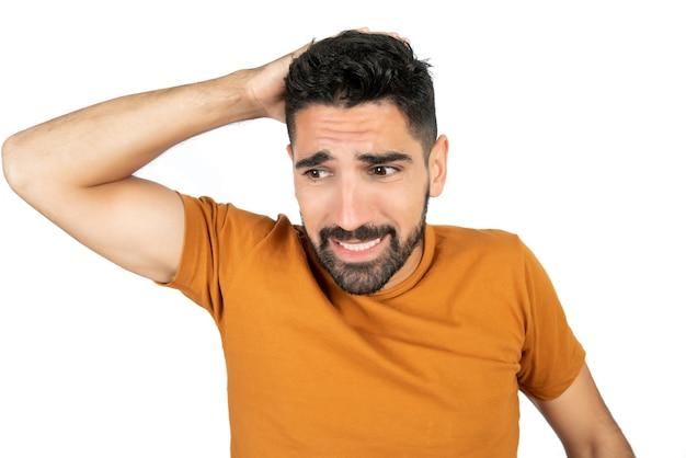 Porträt des jungen mannes, der besorgt über etwas gegen leerraum schaut