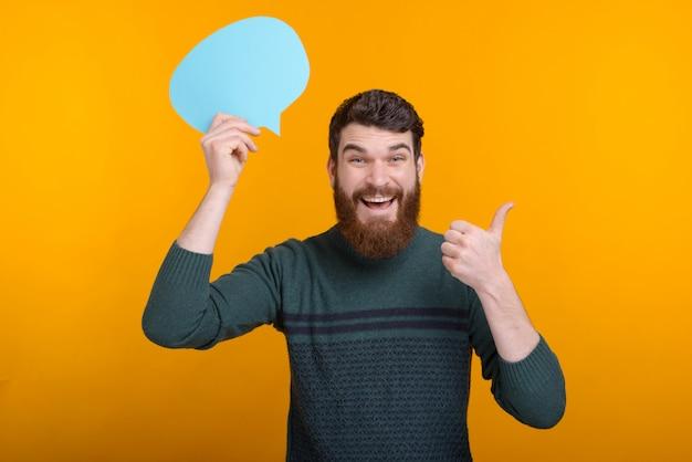Porträt des jungen mannes, der daumen hoch geste zeigt und blaue sprechblase hält