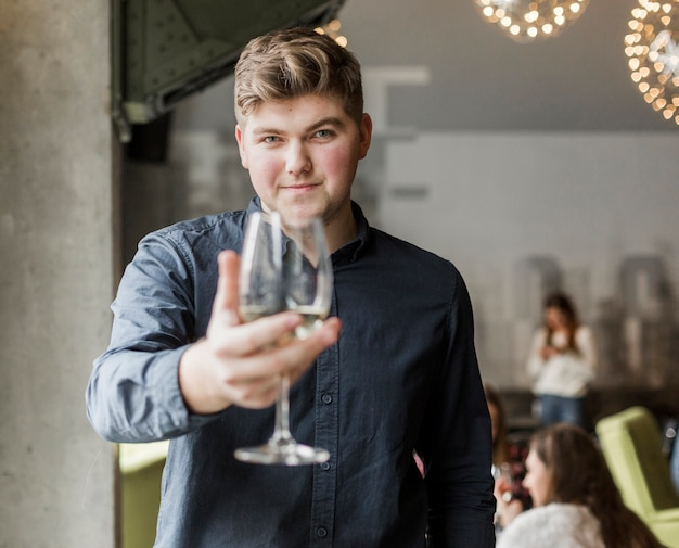 Porträt des jungen mannes, der ein glas wein hält