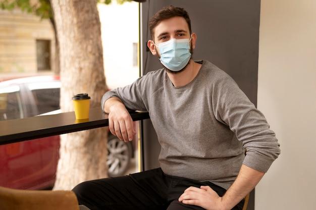 Porträt des jungen mannes, der eine medizinische maske in einem café trägt