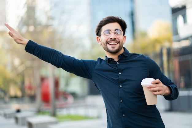 Porträt des jungen mannes, der eine tasse kaffee hält und hand hebt, um ein taxi draußen an der straße zu rufen