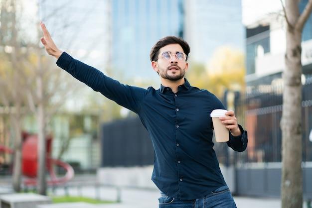 Porträt des jungen mannes, der eine tasse kaffee hält und hand hebt, um ein taxi draußen an der straße zu rufen.