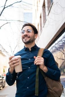 Porträt des jungen mannes, der eine tasse kaffee hält, während draußen an der straße geht. stadt- und lifestyle-konzept.