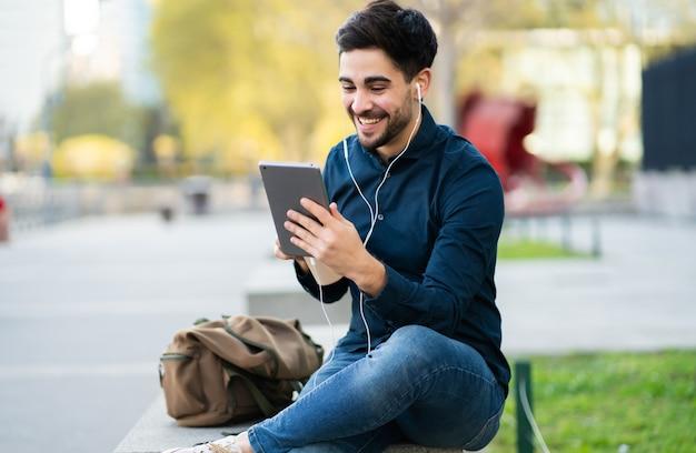 Porträt des jungen mannes, der einen videoanruf auf digitalem tablett beim sitzen auf bank im freien hat. stadtkonzept.