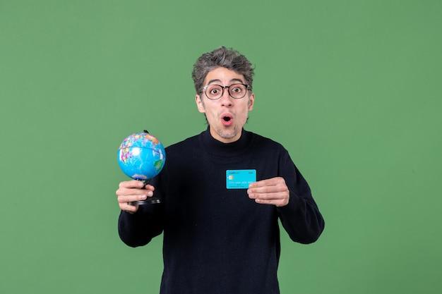 Porträt des jungen mannes, der erdkugel und kreditkarte grüner hintergrund hält luftnaturbanklehrer