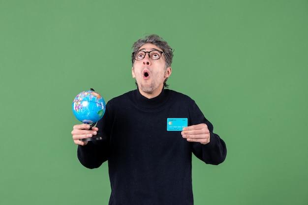 Porträt des jungen mannes, der erdkugel und kreditkarte grüner hintergrund naturbankgeldlehrer hält