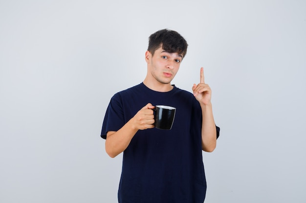 Porträt des jungen mannes, der eureka-geste zeigt, nach oben zeigt, tasse des getränks im schwarzen t-shirt hält und intelligente vorderansicht schaut
