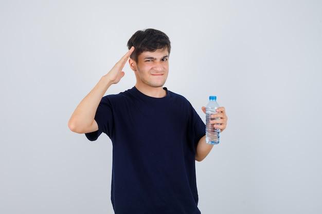 Porträt des jungen mannes, der flasche wasser hält, grußgeste zeigt, lippen spitzt, während in schwarzem t-shirt die stirn runzelt und verwirrte vorderansicht schaut
