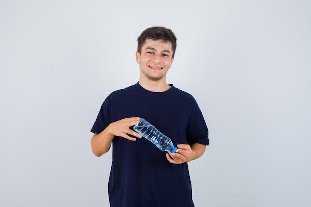 Porträt des jungen mannes, der flasche wasser im schwarzen t-shirt hält und fröhliche vorderansicht schaut