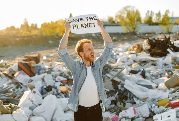 Porträt des jungen mannes, der für die natur kämpft, die das schild der mutter erde auf der müllkippe hält. protestieren gegen die umweltverschmutzung, winken mit den händen, um den planeten zu retten.