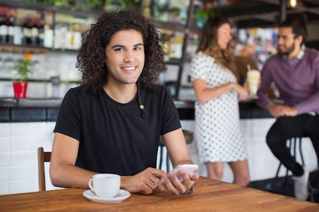 Porträt des jungen mannes, der handy beim sitzen im restaurant hält