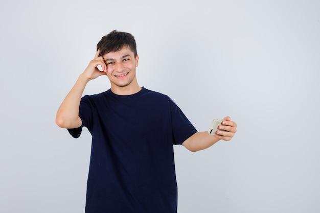 Porträt des jungen mannes, der handy hält, in der denkenden haltung im schwarzen t-shirt steht und fröhliche vorderansicht schaut