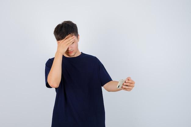 Porträt des jungen mannes, der handy hält, seine stirn im schwarzen t-shirt reibt und deprimierte vorderansicht schaut