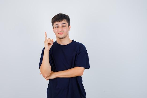 Porträt des jungen mannes, der im schwarzen t-shirt oben zeigt und selbstbewusste vorderansicht schaut