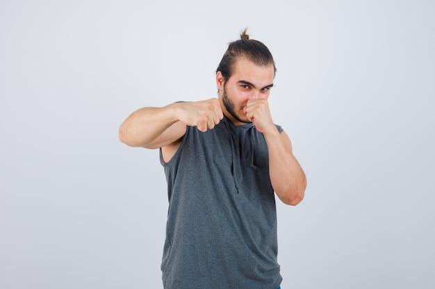 Porträt des jungen mannes, der in der kampfhaltung im ärmellosen kapuzenpulli steht und selbstbewusste vorderansicht schaut