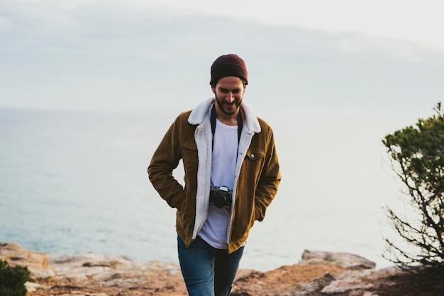 Porträt des jungen mannes, der kamera im freien trägt
