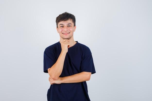Porträt des jungen mannes, der kinn auf hand im schwarzen t-shirt stützt und fröhliche vorderansicht schaut