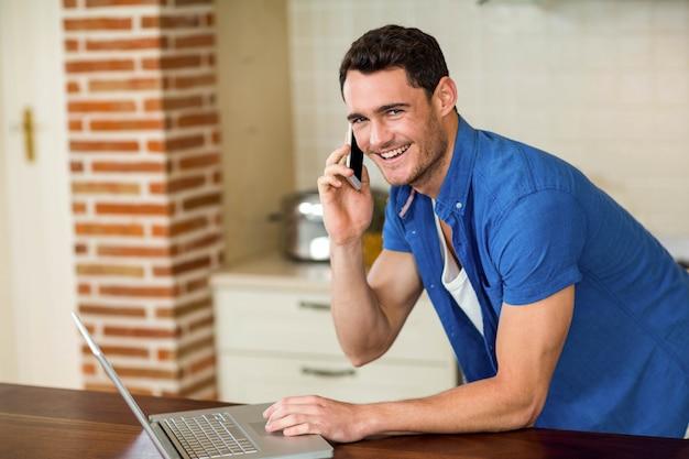 Porträt des jungen mannes, der laptop verwendet und am telefon in der küche spricht
