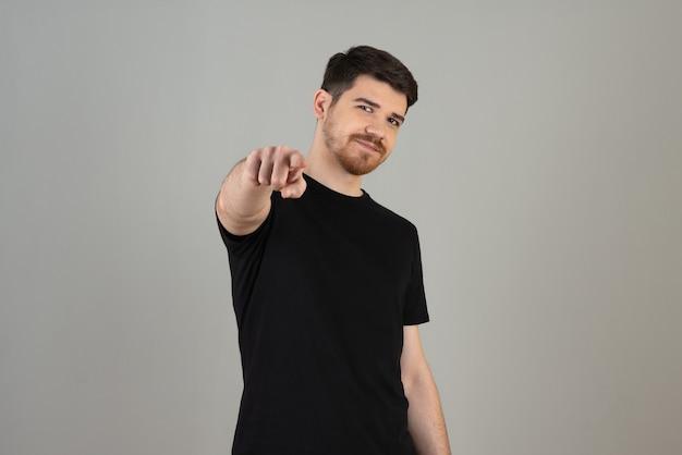 Porträt des jungen mannes, der mit dem finger auf die kamera zeigt.