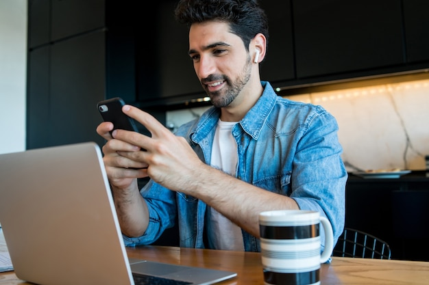 Porträt des jungen mannes, der mit einem laptop arbeitet und sein handy von zu hause aus benutzt. home-office-konzept. neuer normaler lebensstil.