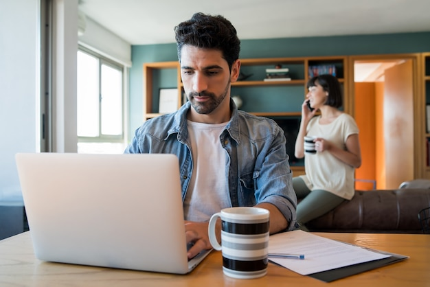 Porträt des jungen mannes, der mit einem laptop von zu hause aus arbeitet, während frau am telefon am hintergrund spricht