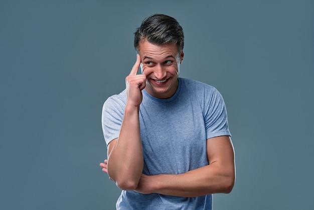 Porträt des jungen mannes, der mit seinem finger gegen das tempelbitten gestikuliert, sind sie verrückt? emotionen, mimik, gefühle, körpersprache, zeichen. bild auf grauem hintergrund.