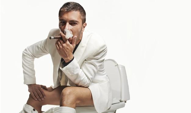 Porträt des jungen mannes der mode, der auf der toilette sitzt