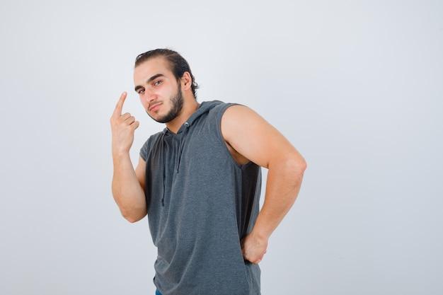 Porträt des jungen mannes, der oben zeigt, während hand auf taille im ärmellosen kapuzenpulli hält und vernünftige vorderansicht schaut