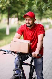 Porträt des jungen mannes, der paket auf einem fahrrad liefert