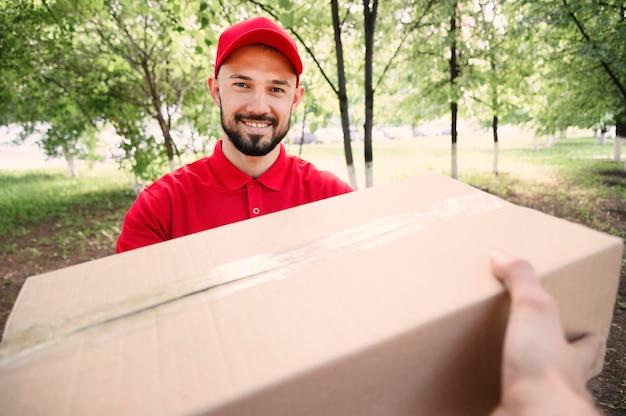 Porträt des jungen mannes, der paket liefert