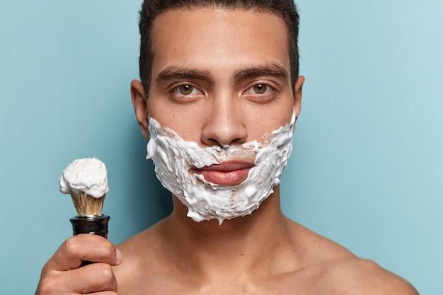 Porträt des jungen mannes, der rasierschaum anwendet