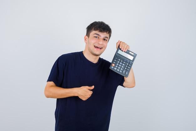 Porträt des jungen mannes, der rechner hält, daumen oben im schwarzen t-shirt zeigt und erfreute vorderansicht schaut