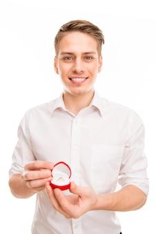 Porträt des jungen mannes, der rote box mit ehering hält
