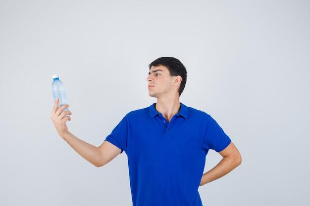 Porträt des jungen mannes, der schlacht hält und es im t-shirt betrachtet und sorgfältige vorderansicht betrachtet