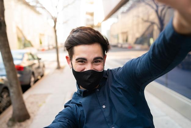 Porträt des jungen mannes, der schutzmaske trägt und ein selfie nimmt, während draußen auf der straße stehend. neues normales lifestyle-konzept.